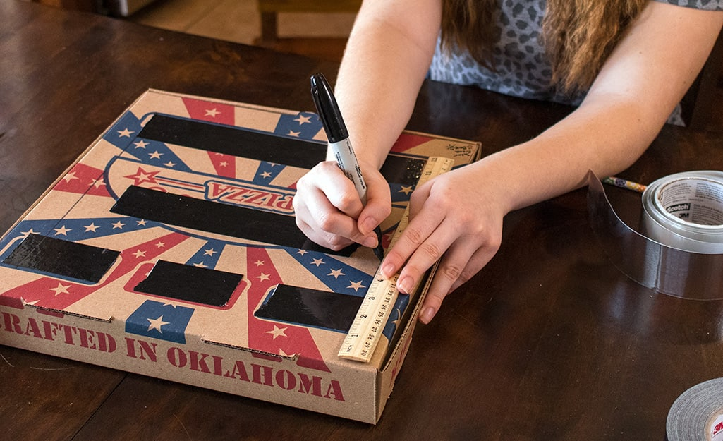 A person drawing lines on a pizza box.