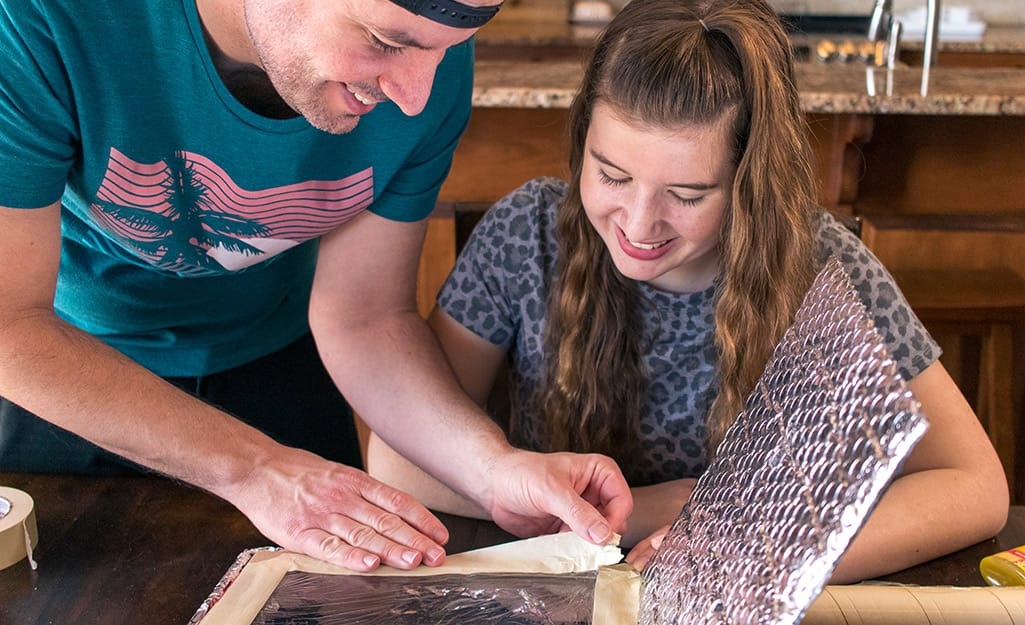 Two people adding tape to the inside of a pizza box.