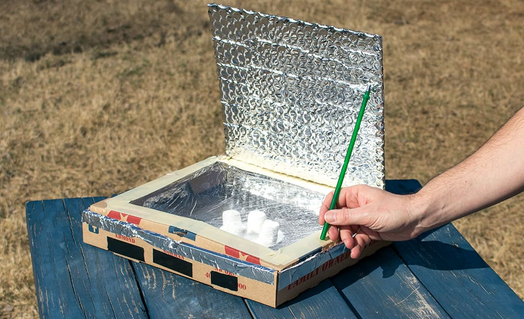 A person placing a pencil to prop open a lid of a homemade solar oven.