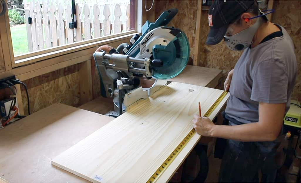 A woman uses a miter saw to cut plywood board.