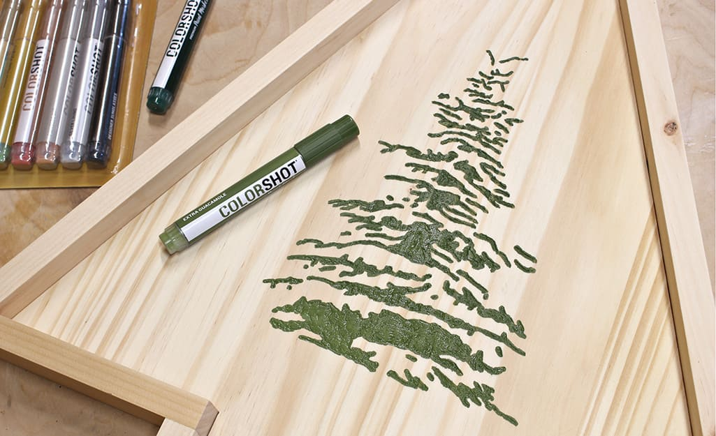 A color pen is used to add green color to carved design.