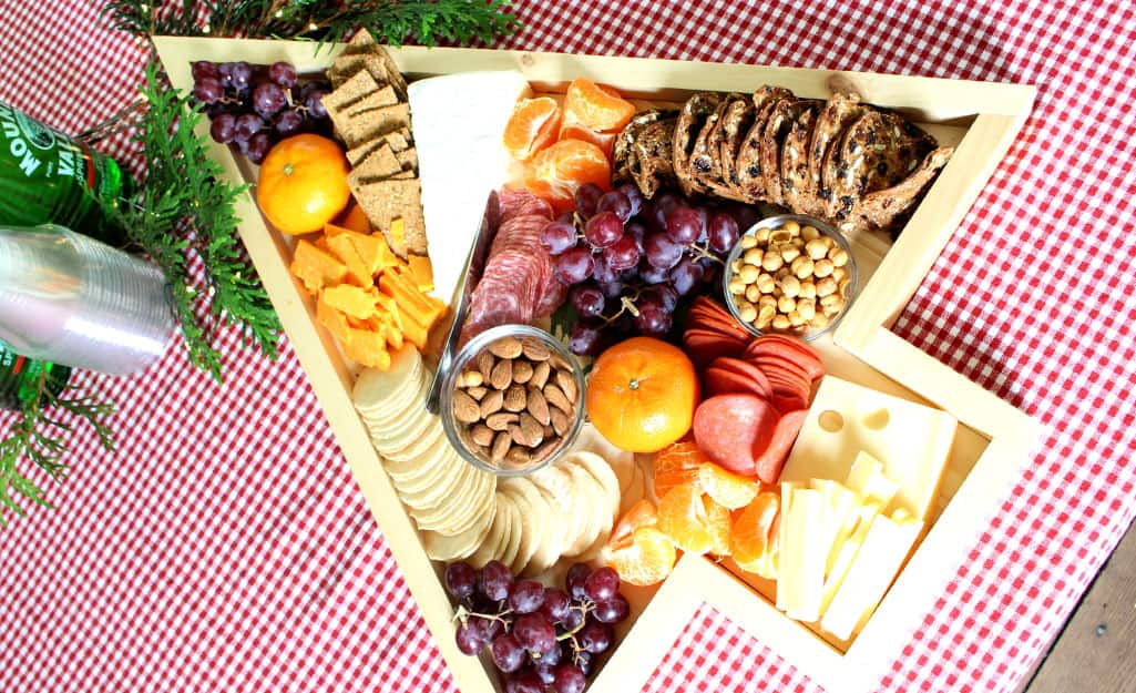 A finished charcuterie board holds fruit, cheese and crackers.