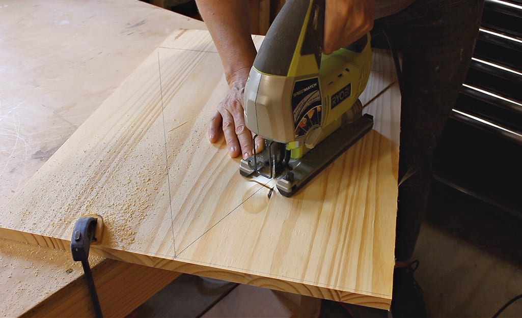 A person uses a jig saw to cut a tree shape on a board.