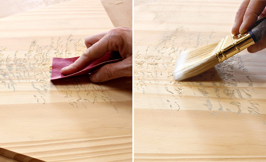 A person uses sandpaper to sand and a paint brush to remove dust from board.