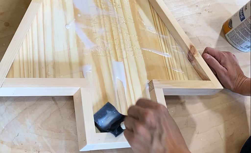 A foam brush is used to apply stain to the board.