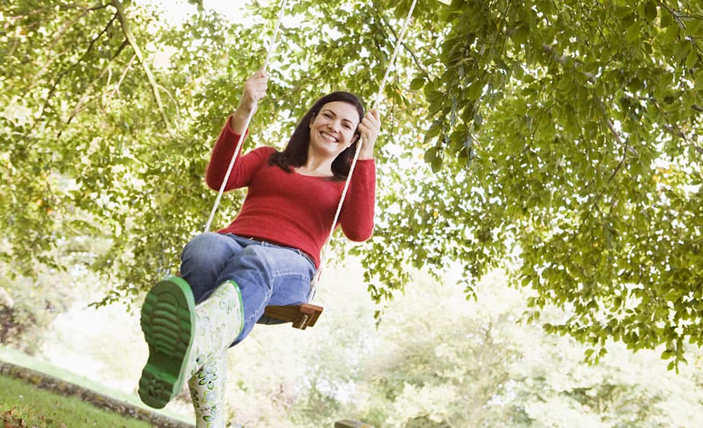 An adult swinging in a tree swing to test that it is secure.