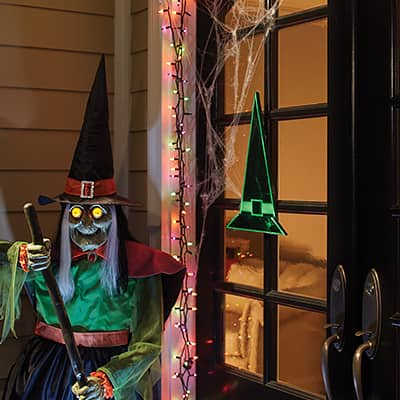 Two wooden witches hats hanging on a front door among assorted Halloween decor.