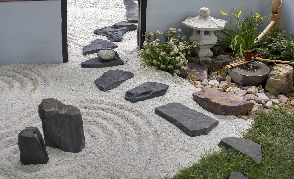 A Zen garden with circles traced in crushed white gravel, a stone lantern, some plants and black rocks and stepping stones.