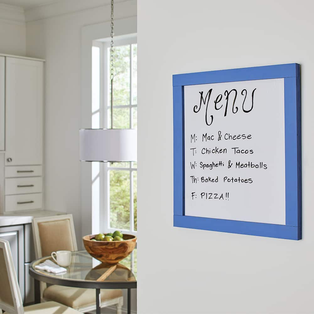 A dry erase menu board hangs in a sunny kitchen.
