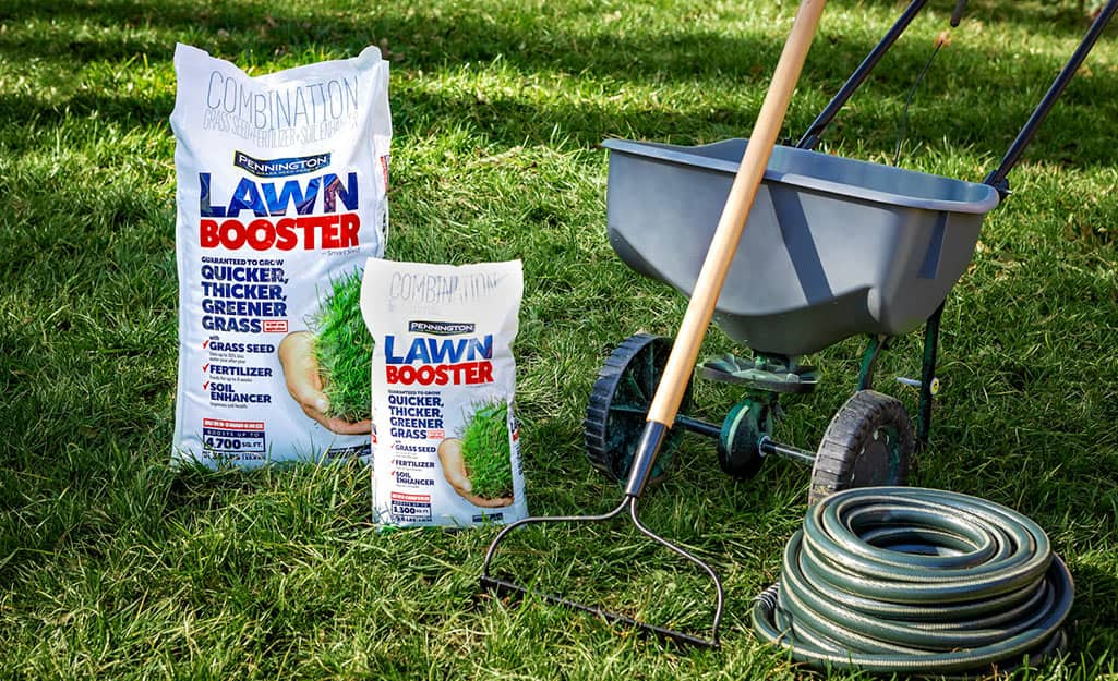 Bags of lawn fertilizer, a rake, a garden hose and a wheelbarrow sit on a green lawn.