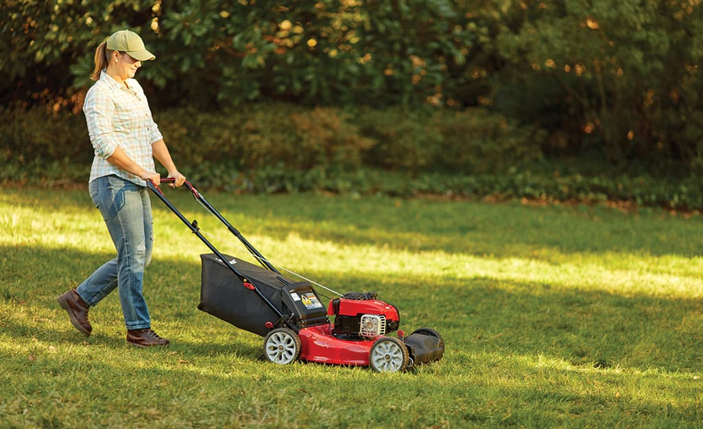 Someone uses a push mower to mow a lawn.
