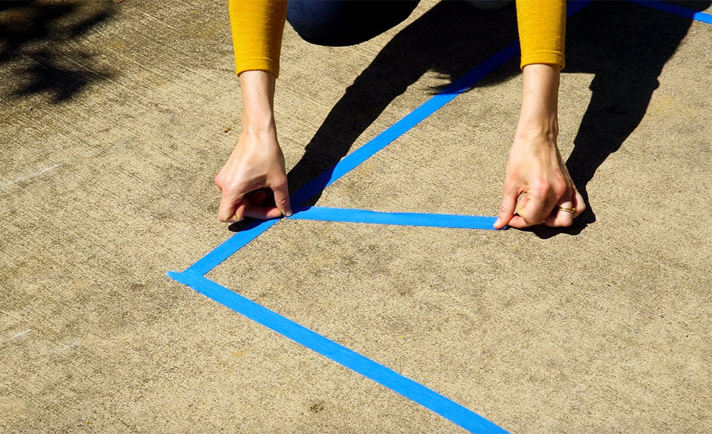 A woman uses painter's tape to outline her design.