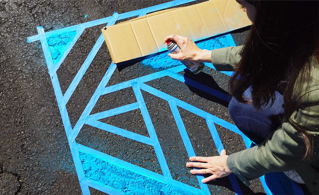 A woman uses a piece of cardboard to keep colors separate in design.