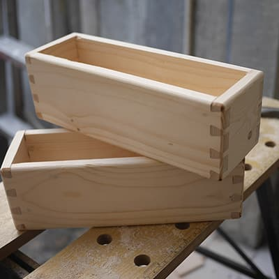 Wooden boxes with dovetail joints arranged on a workbench.
