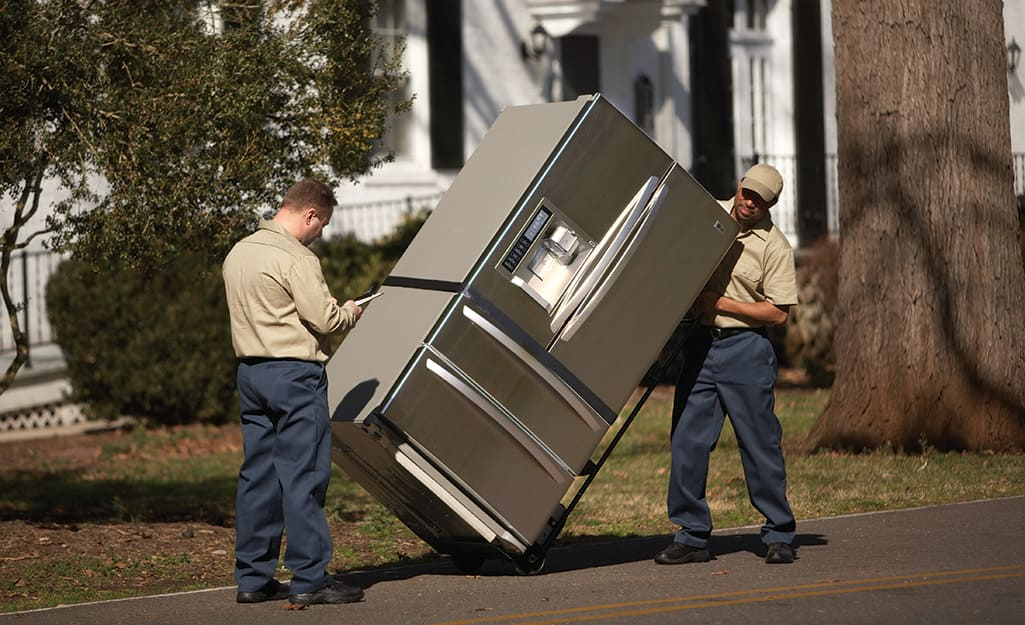 Two people moving a refrigerator.