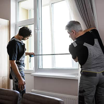 Two people measuring a window.