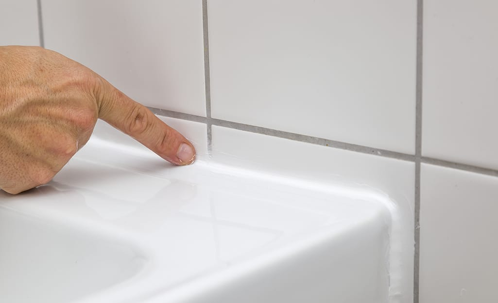 A hand puts to the caulk in the joint between a sink and a tile wall.