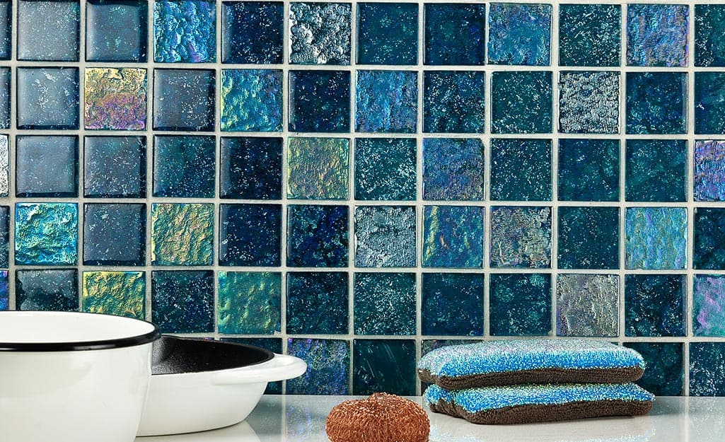 Kitchen backsplash made with blue, iridescent tiles and white grout.
