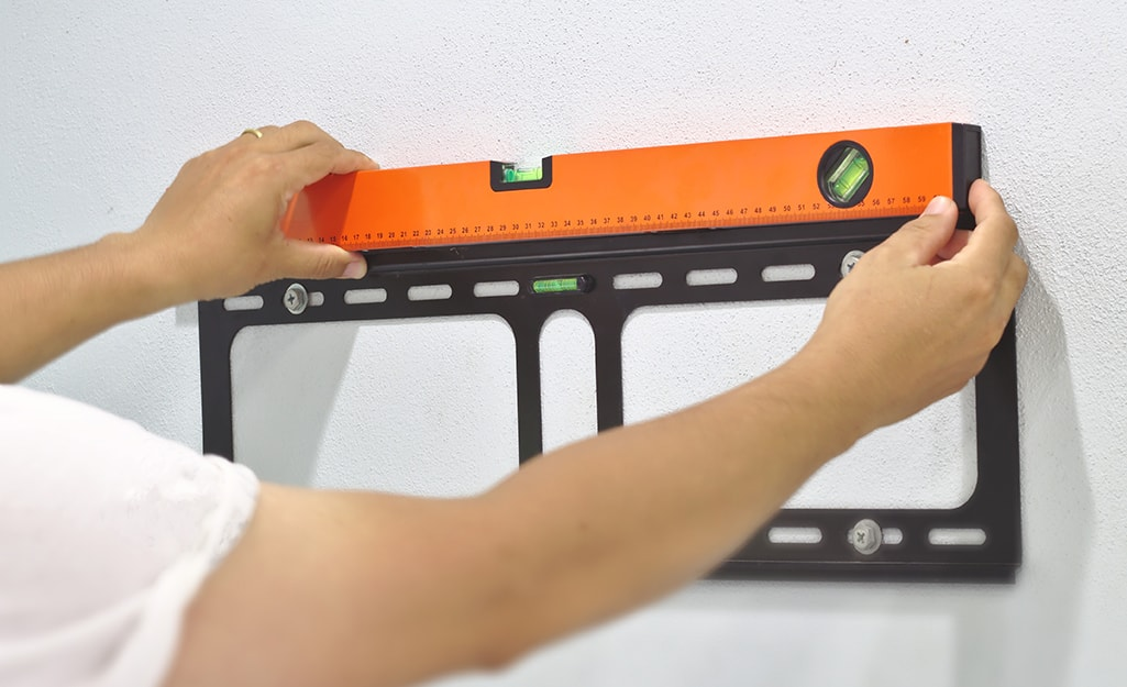A level being used to mark placement for wall mount.
