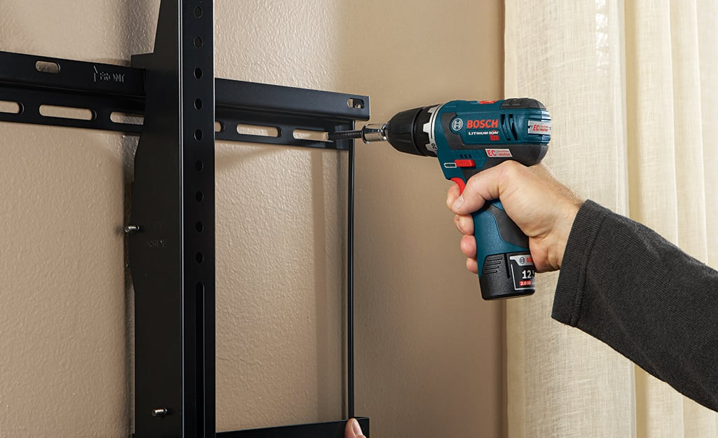 A person drilling screws into the wall mount fixture.