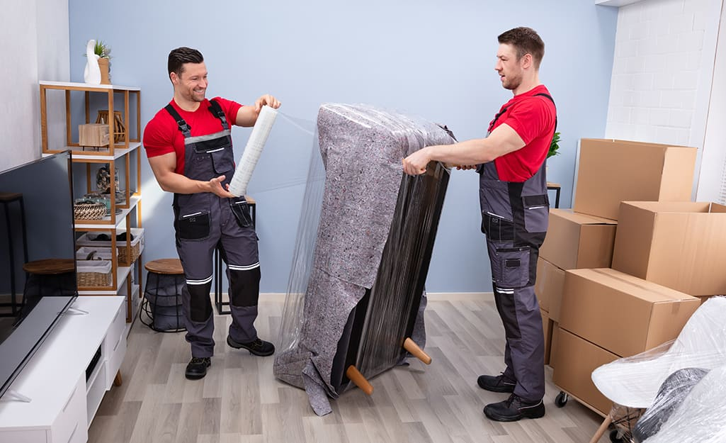 Two professional movers wrap a couch.