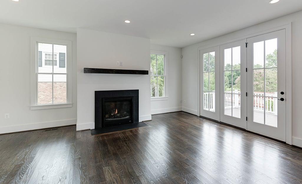An empty living room with dark wood floor.