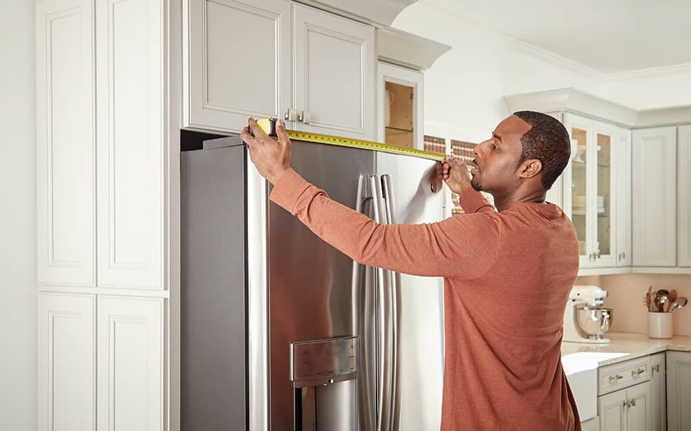 A person measuring a refrigerator.