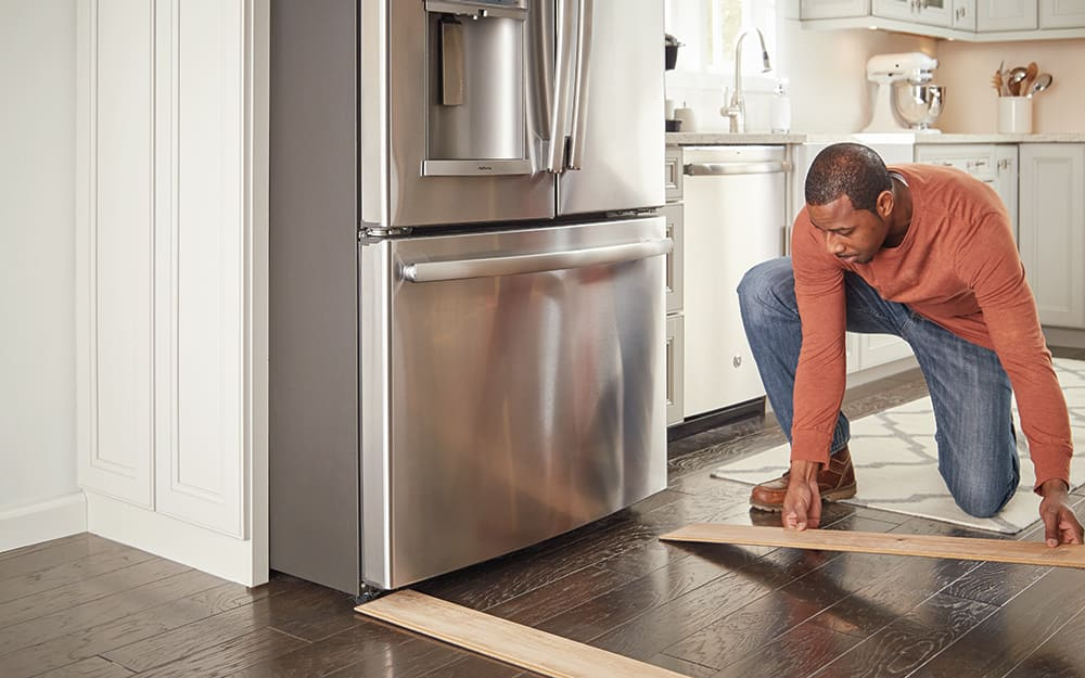 A person laying vinyl planks to protect floors while moving a refrigerator.