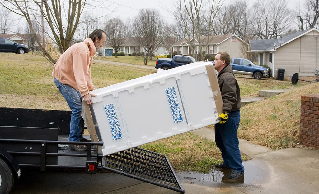 Two people loading a refrigerator onto a truck.