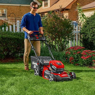 Man using a push mower to mow a lawn.