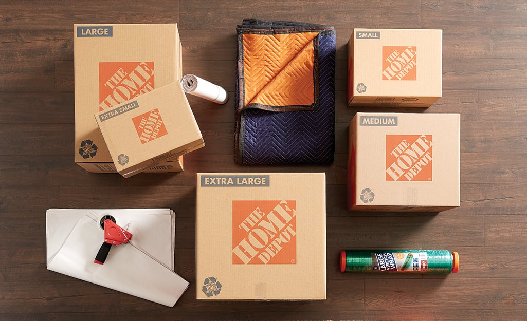 Home Depot boxes, moving blankets and packing paper lying on a wood floor.