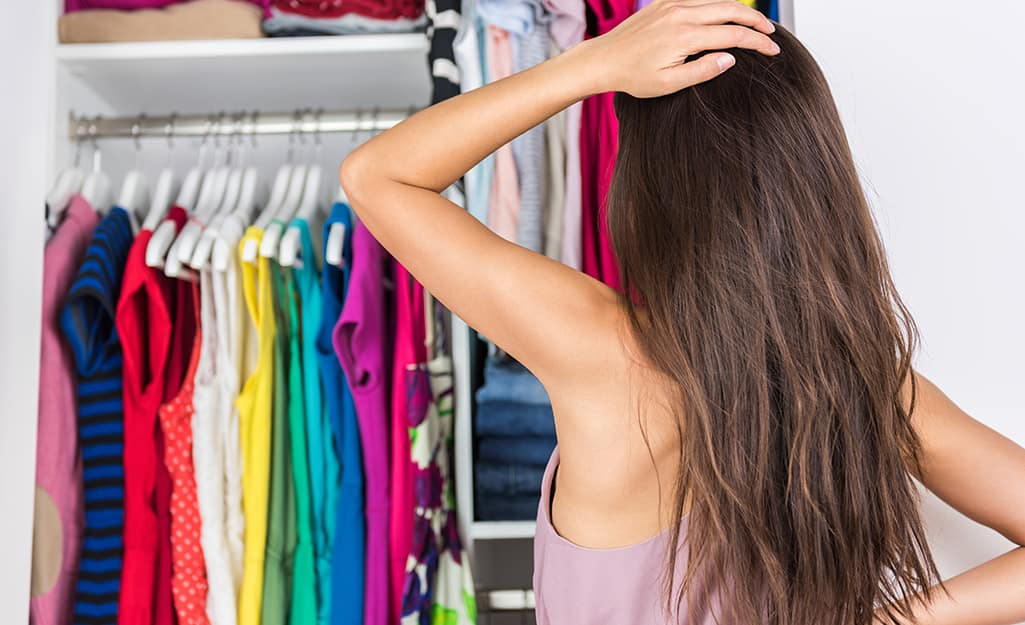 Woman staring into a full closet.