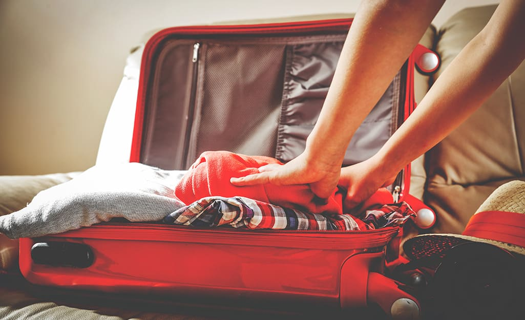 Someone packing a suitcase with clothes.