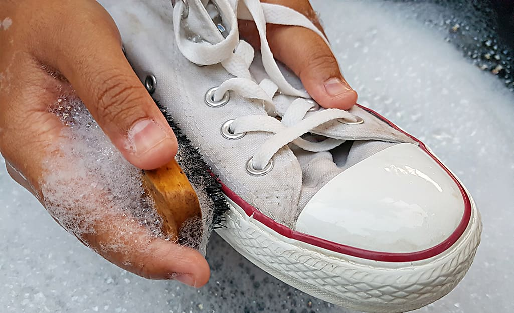 Person washing athletic shoes with brush and soapy water.