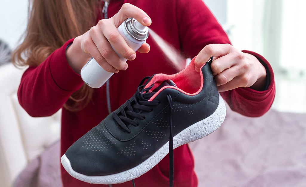 Someone spraying a sneaker with deodorizing spray.