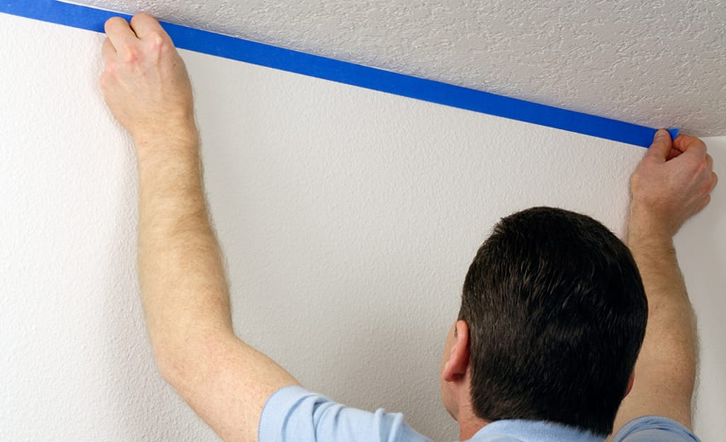 A man uses painter's tape to prep the walls before painting the ceiling.
