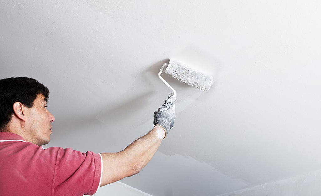 A man begins to paint the ceiling white using a roller.