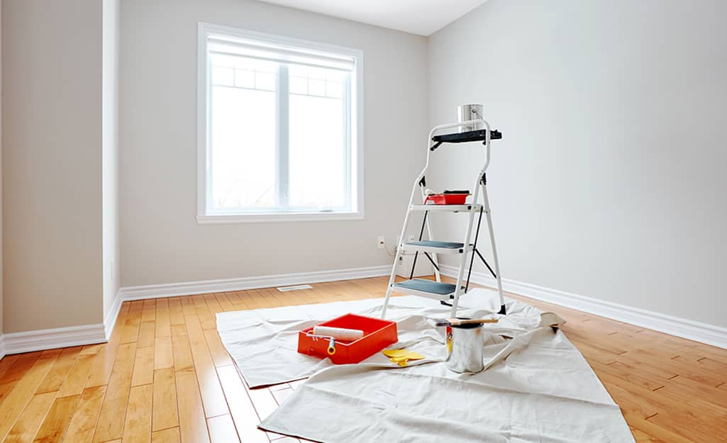 A step ladder and other paint supplies stand in a painted room.