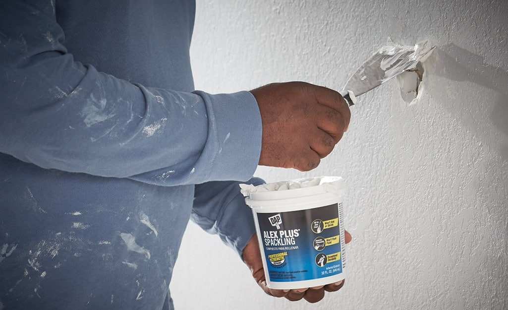 A person applying spackling compound to a wall.