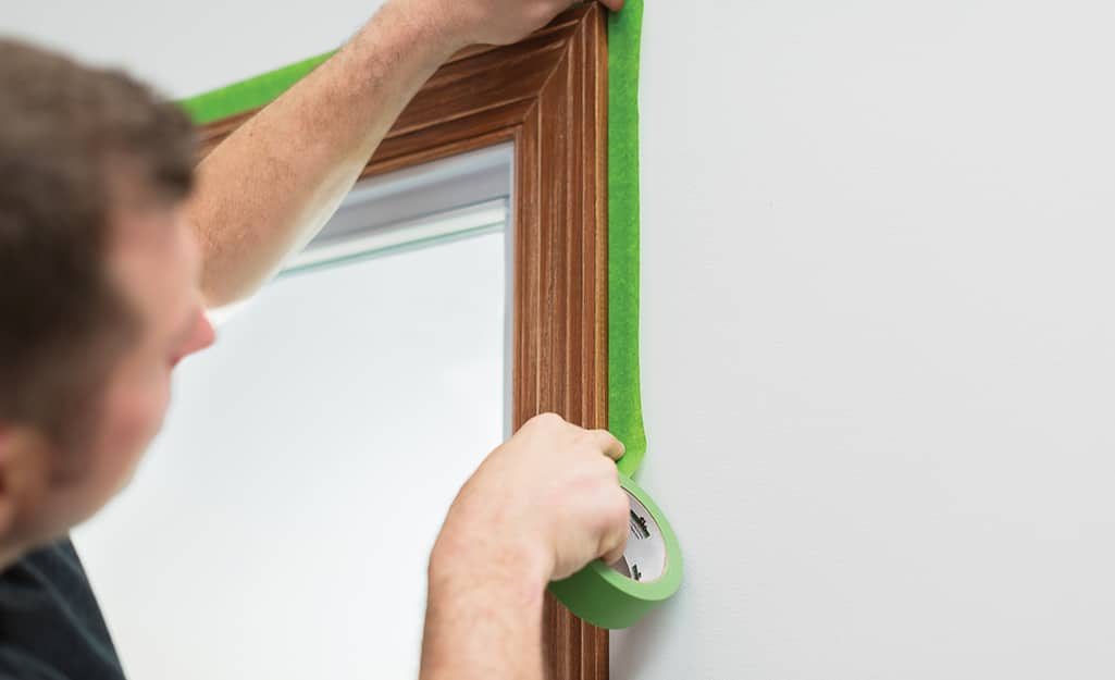 A person applying painter's tape around a door frame.