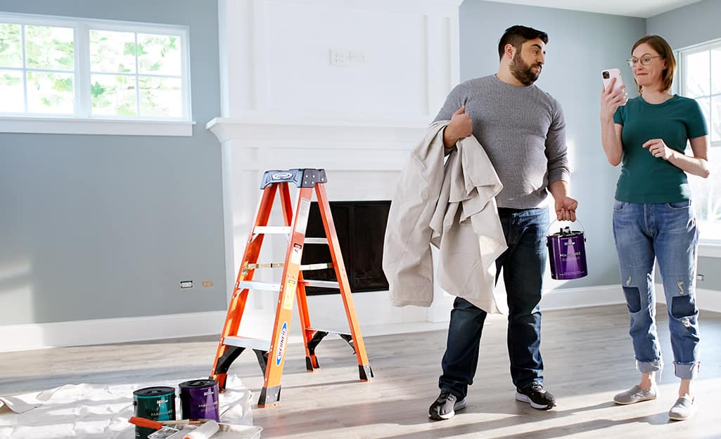 A man and a woman holding paint supplies.