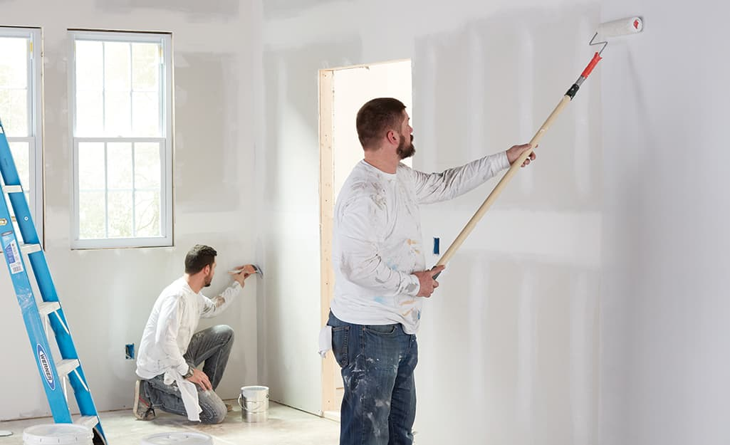 Two men painting a wall in a room.
