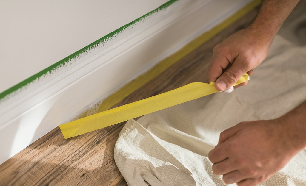 A person removing the tape from a baseboard.