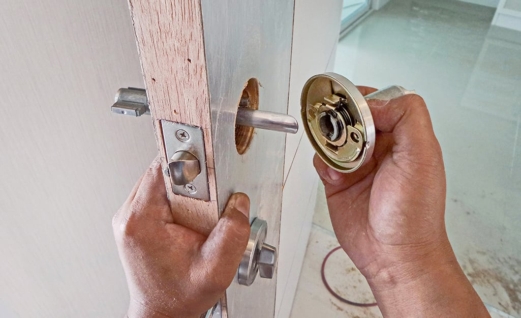 A person removes doorknob hardware from a door.