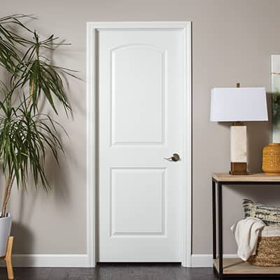 A white door with white trim in a living space.