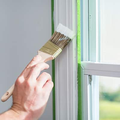 A person painting interior trim around a window.