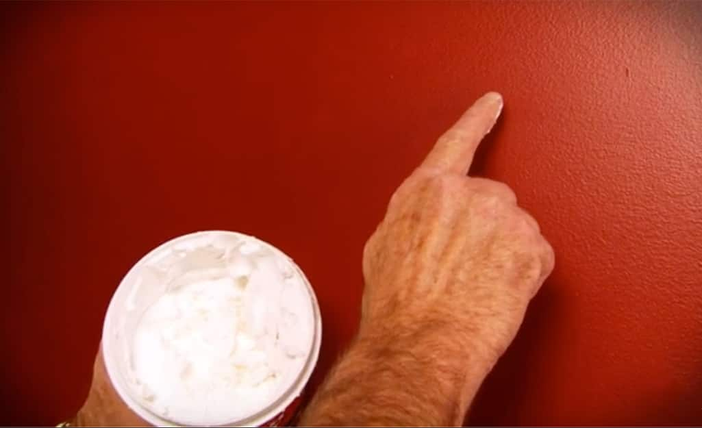 A person applying joint compound to a wall.