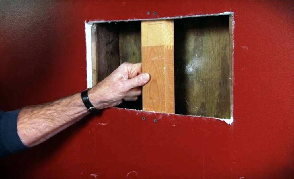 A person installing a wood support behind an opening in drywall.