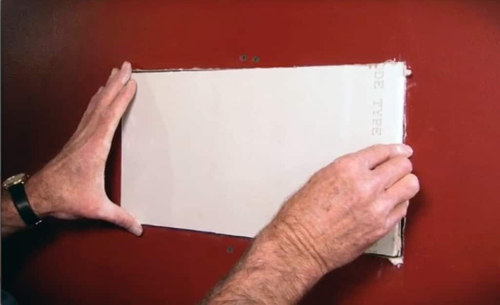 A person fitting a drywall patch into a wall.