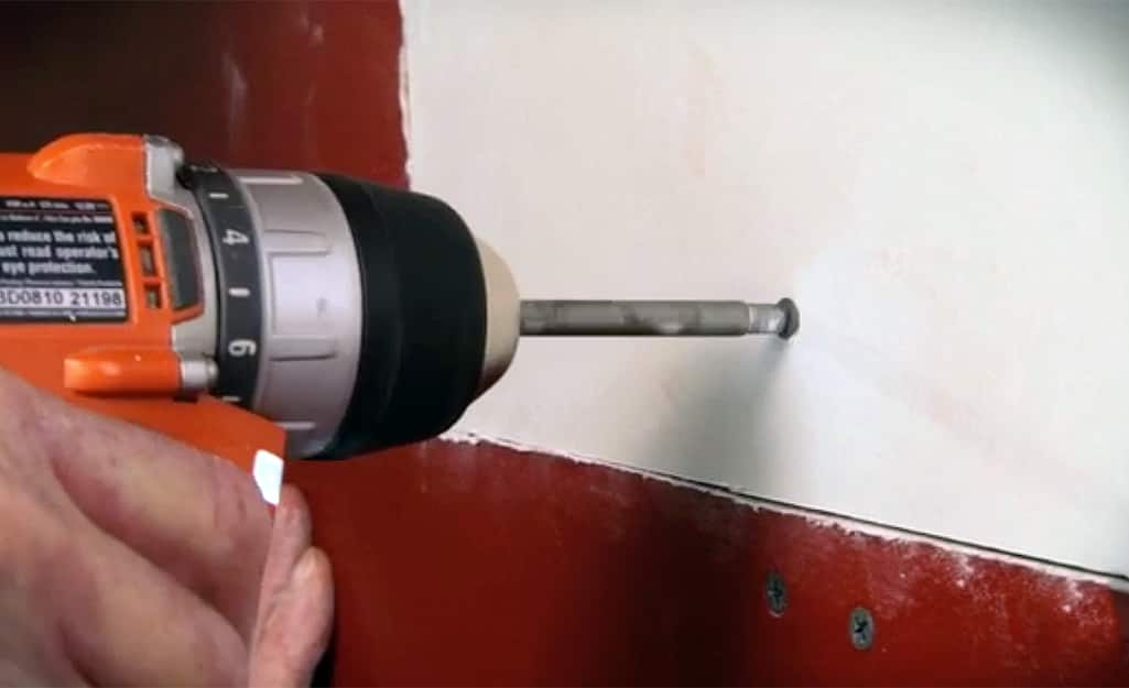 A person drilling a drywall screw into a drywall patch in the wall.